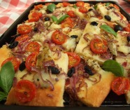 Gluten free pizza with tomatoes, olives, artichokes, onion, and mozzarella
